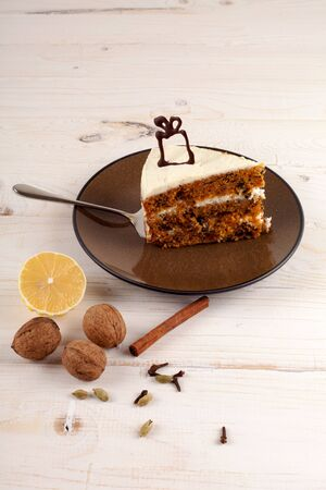 carrot cake: A piece of carrot cake with walnuts and white cream,  with chocolate present  on top. Stock Photo