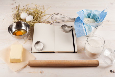 Ingredients for the dough with a book for recipes for Easter. Eggs, flour, butter, sugar and kitchen tools on a white wooden background. Rustic background with free text space.
