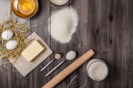 Ingredients for the dough for Easter. Eggs, flour, butter, sugar and kitchen tools on a dark wooden background. Rustic background with free text space. Flat lay. Top view. Stock Photo