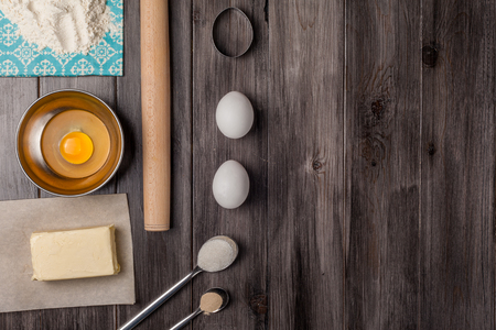 Ingredients for the dough for Easter. Eggs, flour, butter, sugar and kitchen tools on a dark wooden background. Rustic background. Flat lay. Top view.
