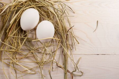 Easter eggs in the halm, lies on a white wooden background