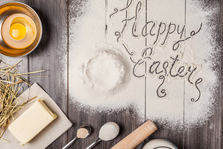 Ingredients for the dough and baking with the words Happy Easter in the center of composition. Eggs, flour, butter, sugar and kitchen tools on a dark wooden background. Rustic background. Flat lay.