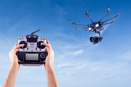 Hands of a man with a radio control drone on a background of beautiful blue sky. Remote radio control copter in the young mans hands. Management of professional drone Stock Photo
