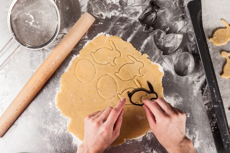 The process of making fragrant Easter cookies with spices and honey from the dough. Woman cuts dough figures ducks, eggs, rabbits using forms. View from above.