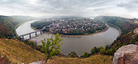 top 7: Panoramic views of the river Dniester and the city Zalishchyky. Ternopil region. Ukraine. Zalishchyky City, surrounded by the river Dnest in the shape of a horseshoe, with a bridge across the river. Autumn landscape. Stock Photo
