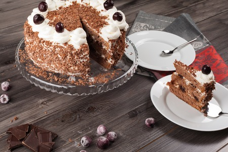 cake plate: Black forest cake decorated with whipped cream, cherries and with chocolate chips on a dark wooden background.
