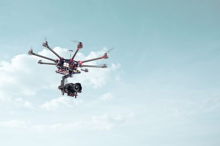 rc: Copter shoots in flight on a background of beautiful blue sky. RC aircraft in the sky. Stock Photo