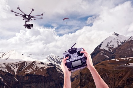 mules: In the hands of a professional radio control mules on the background of beautiful mountains. Remote radio control copter in the young mans hands. Management of professional drone