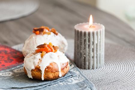 frutos secos: pastel de Pascua rica en frutas secas y una vela encendida sobre un fondo gris. Foto de archivo