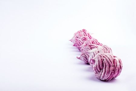 blackcurrant: Delicious homemade sweet pink marshmallow with blackcurrant, dusted with icing sugar on a white background.