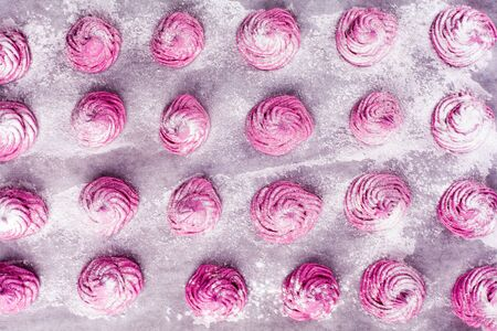 blackcurrant: Delicious homemade sweet pink marshmallow with blackcurrant, dusted with icing sugar on a white background. Cooking process. Top view. Stock Photo