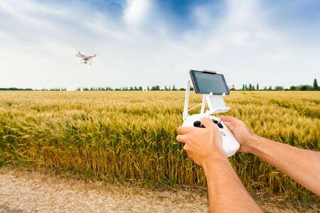 Demostración de helicóptero no tripulado. El hombre controla quadrocopter vuelo. Volar el helicóptero sobre un campo de trigo. Control remoto en manos de un hombre. Foto de archivo - 59128208
