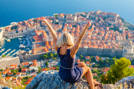 Young female traveler looks to the old city and sea from mountain in Dubrovnik. Croatia.