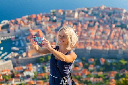 Feminino viajante fazer uma foto de selfie no contexto da cidade velha de Dubrovnik da montanha Foto de archivo - 60923650