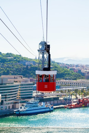 montjuic: Red cabin cable car against the background of the city of Barcelona. View overlooking the town.