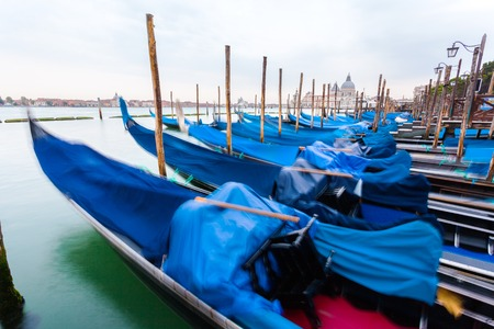 Pier gondolas near Piazza San Marco in Venice at sunrise. A number of boats on the background of the waterfront in Venice. Italy
