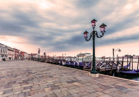 reverent: Waterfront of Venice at sunrise. Riva degli Schiavoni. Berth with gondolas at dawn near the San Marco square. Italy. Stock Photo