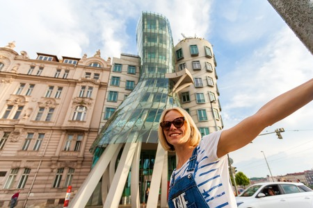 dancing house: PRAGUE, CZECH REPUBLIC - JUNE 04, 2016: Happy young female traveler swirls around a traffic lighter in front of the Dancing House. Blonde girl having fun in the street near Dancing House. Europe.
