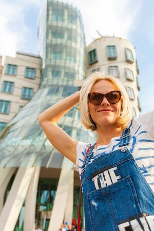 PRAGUE, CZECH REPUBLIC - JUNE 04, 2016: Happy young female traveler swirls around a traffic lighter in front of the Dancing House. Blonde girl having fun in the street near Dancing House. Europe.