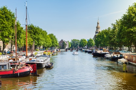 boat house: Typical street in Amsterdam with canal, colorful houses and water boat house in the Dutch style. Netherlands. Stock Photo