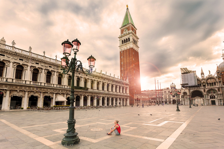 st mark's square: Girl female traveler sitting on the Piazza San Marco in Venice at sunrise and enjoy the area without people. The main square of the old town. Italy.