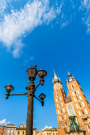 Fragment of Church of St. Mary in the main Market Square with lamppost and pigeons in the foreground. Basilica Mariacka. Krakow. Poland. Stock Photo