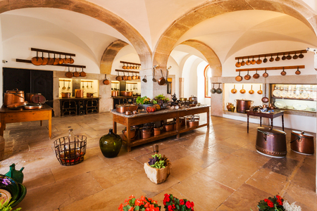 rustic kitchen: SINTRA, PORTUGAL - JULY 12, 2015: Old country style kitchen with fireplace and copper pans in bright colors with arches. Interior.