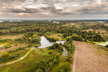 backwater: Autumn landscape with dramatic sky in the background in rich colors from above. Aerial view. Outdoor. Lush green field with river and backwater skyline. Stock Photo