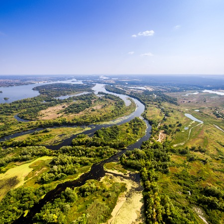 backwater: Summer landscape in rich colors from above. Aerial view. Outdoor. Lush green field with river and backwater skyline.