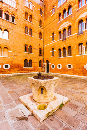 redbrick: A small Square Adriano with red-brick building in Venetian style with a well in Venice. Italy
