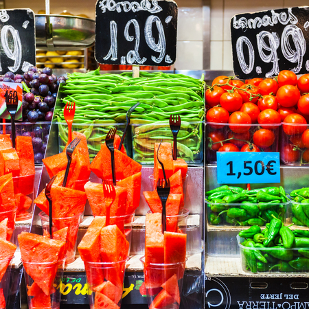 Colourful fruit and vegetables at market stall in Boqueria market in Barcelona. Batch containers with watermelon, grapes, asparagus, tomato and green pepper.
