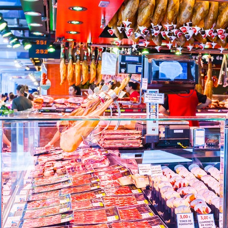 BARCELONA, SPAIN - AUGUST 25, 2016: Well known Boqueria Market in Barcelona. Jamon - spanish word for ham - traditional meat in spanish cuisine. Countertop with different food products made in Spain. Editorial