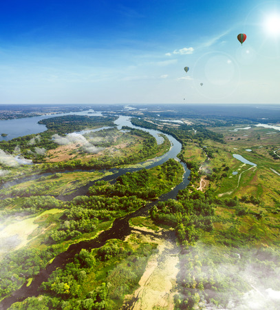 backwater: Summer landscape in rich colors from above with balloons in the background. Aerial view. Outdoor. Lush green field with river and backwater skyline.