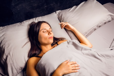 sweetly: Woman sleeping in bed on a dark background. Beautiful young brunette sleeping sweetly in bed. Stock Photo