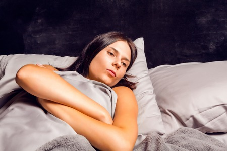 sulk: Woman lying in bed on a dark background with open eyes. Beautiful young brunette in bad mood lying in bed.