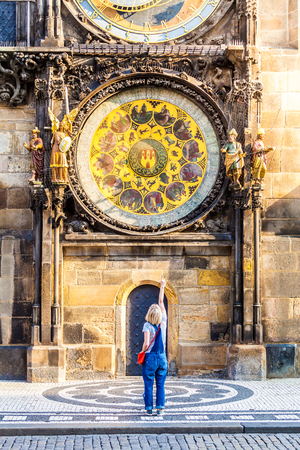 Young female traveler refers to the astronomical clock in the Old Town Hall - the national symbol of Prague. Czech Republic. Stock Photo