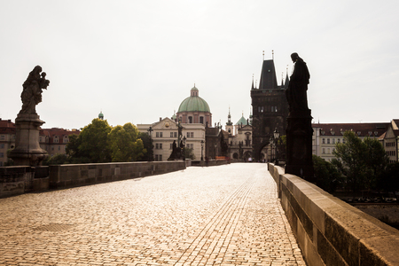 francis: Prague, Czech Republic. Charles Bridge with its statuette, Old Town Bridge Tower, St. Francis Of Assissi Church in the background. Stock Photo