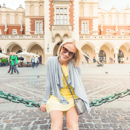 spectacled: Young female tourist sitting on a chain link fence in an area near the Cloth Hall in Krakow.