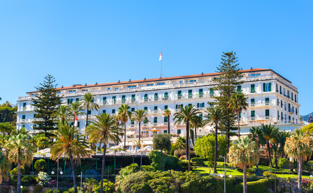 The building is famous hotel in San Remo, Italy. Beautiful historic building on the waterfront in the lush garden.