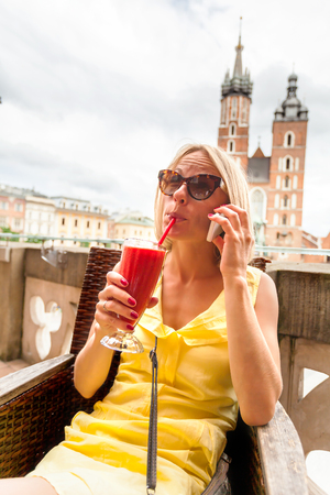 A woman drinking a cocktail on the terrace of a cafe and talking on the phone in front of St Marys church in Krakow. Poland.