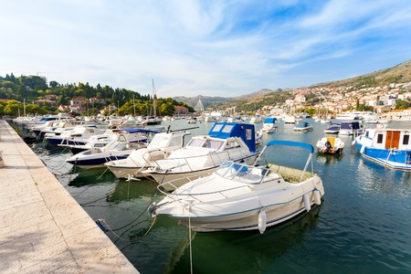 Beautiful sunny day over the bay in front of old town of Dubrovnik. Pier with boats. Stock Photo