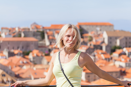 Beautiful young blonde girl on a background of blurred panorama of Dubrovnik old town. Beautiful view of the walled city, Dubrovnik Croatia. The mysterious atmosphere and processing.
