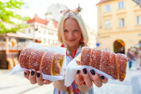 galletas: Turista femenino joven con el postre tradicional checa llama trdelník en Praga. República Checa. Al aire libre
