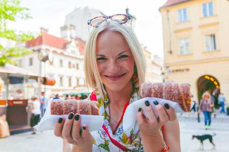 Young female tourist with traditional czech dessert called trdelnik in Prague. Czech Republic. Outdoor