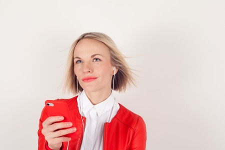 Portrait of a woman with headphones and mobile phone in hand in red jacket on white background. The emotion of happiness. Girl dancing to the music