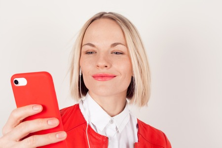 Portrait of a woman with headphones and mobile phone in hand in red jacket on white background. The emotion of happiness.