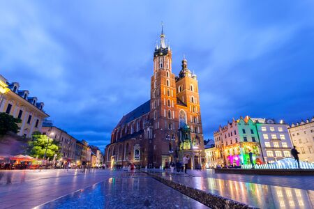 St. Marys Church at night. Market Square - main square in old city. Krakow Poland.