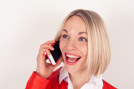 Portrait of a woman talking on a mobile phone in a red jacket on a white background. The emotion of surprise Stock Photo