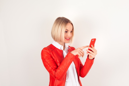 Portrait of a woman with mobile phone in a red jacket on a white background. The emotion of surprise