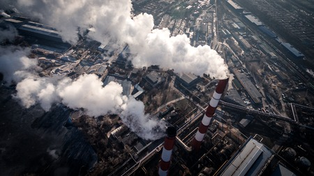 Air pollution by smoke coming out of two factory chimneys. Aerial view